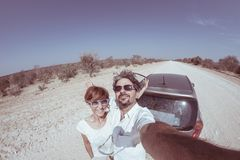 Adult couple selfie on road trip in the desert, Namib Naukluft National Park, travel destination in Namibia, Africa. Fisheye, peop Royalty Free Stock Photo