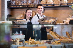 Adult couple selling pastry and loaves. Adult couple selling fresh pastry and loaves in bread section stock image