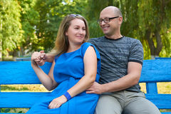Adult couple sit on bench in city park, summer, romantic and love concept, happy people man and woman Stock Photography