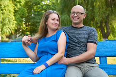 Adult couple sit on bench in city park, summer season, romantic and love concept, happy people man and woman Stock Image