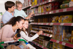 Adult couple with small kids  purchasing jam. In hypermarket and smiling. Focus on woman Stock Image