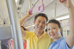 Adult couple standing in the subway and smiling, portrait, looking at camera stock image