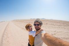 Adult couple taking selfie on gravel road in the Namib desert, Namib Naukluft National Park, main travel destination in Namibia, A Stock Photo