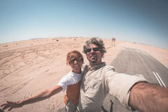Adult couple taking selfie on road in the Namib desert, Namib Naukluft National Park, main travel destination in Namibia, Africa. Fisheye view Stock Images