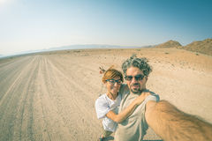 Adult couple taking selfie on road in the Namib desert, Namib Naukluft National Park, main travel destination in Namibia, Africa. Stock Images