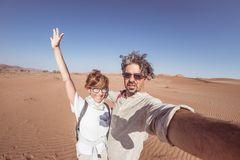 Adult couple taking selfie on sand dunes at Sossusvlei in the Namib desert, Namib Naukluft National Park, main travel destination. In Namibia, Africa. Fisheye Royalty Free Stock Image