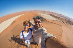 Adult couple taking selfie on sand dunes at Sossusvlei in the Namib desert, Namib Naukluft National Park, main travel destination. In Namibia, Africa. Fisheye Royalty Free Stock Photography