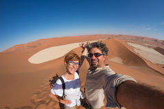 Adult couple taking selfie on sand dunes at Sossusvlei in the Namib desert, Namib Naukluft National Park, main travel destination. In Namibia, Africa. Fisheye Stock Photos