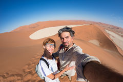 Adult couple taking selfie on sand dunes at Sossusvlei in the Namib desert, Namib Naukluft National Park, main travel destination. In Namibia, Africa. Fisheye Royalty Free Stock Photo