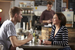 Adult couple talking at a table in a coffee shop, side view Stock Photos