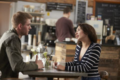 Adult couple talking at a table in a coffee shop, side view Stock Photo