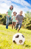 Adult couple and teenager playing with soccer ball Royalty Free Stock Images