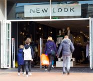 An adult couple and two children walking into a New Look shop. Two adults and two children walking into a New Look store Stock Image