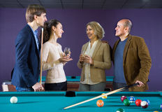 Adult couples of different generations talk in the billiard room Royalty Free Stock Photo