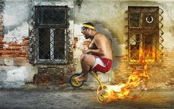 Adult crazy man cycling on child's bicycle Royalty Free Stock Photos