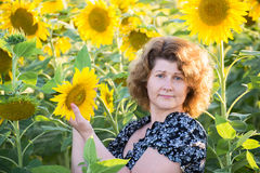 Adult curly-haired woman in field of sunflowers Royalty Free Stock Photography