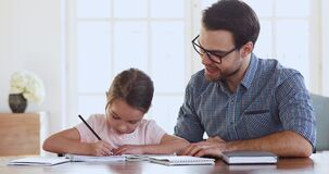 Dad and child daughter studying together giving high five