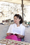 Adult dark-haired woman, reading a book Royalty Free Stock Images