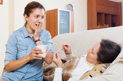 Adult daughter caring for a sick mother Royalty Free Stock Image