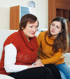 Adult daughter  comforting sad mature woman Stock Images