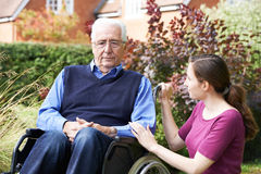 Adult Daughter Comforting Senior Father In Wheelchair Stock Image