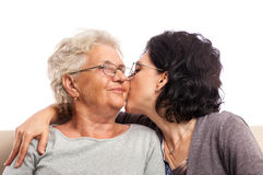 Adult daughter giving old mom a kiss Stock Photos