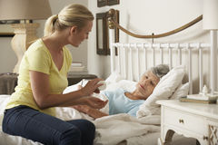 Adult Daughter Giving Senior Female Parent Medication In Bed At Home Stock Photos