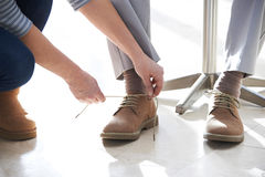 Adult Daughter Helping Senior Man Tie Shoelaces. Adult Daughter Helps Senior Man Tie Shoelaces royalty free stock photo