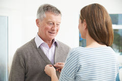 Adult Daughter Helping Senior Man To Button Cardigan. Adult Daughter Helps Senior Man To Button Cardigan Stock Photos