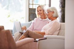 Adult Daughter Helping Senior Mother With Computer At Home Royalty Free Stock Photos