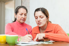 Adult daughter helps the mother to fills in  bills Stock Photos