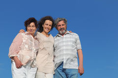 Adult daughter and her parents embracing Stock Photography