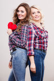 Adult daughter and mother with heart love sign. Generation relationship mother`s day concept. Adult daughter and mother posing with red heart shape love symbol Stock Photography