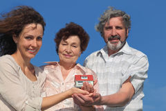 Adult daughter and parents holding house model Royalty Free Stock Photos
