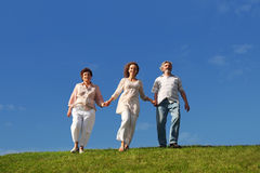 Adult daughter and parents walking on lawn Stock Image