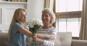 Adult daughter presenting flowers congratulating hugging old mother, portrait