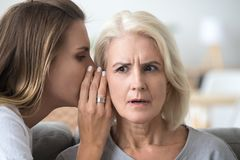 Adult daughter share secret with surprised aged mom royalty free stock photo