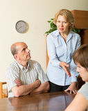 Adult daughter talking with parents. Adult daughter and elderly parents having serious talking at home stock image