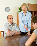 Adult daughter talking with parents. Adult daughter having serious talking with elderly parents at home royalty free stock photos