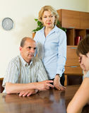 Adult daughter talking with parents. Adult daughter having serious talking with elderly parents at the table at home royalty free stock image