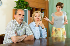 Adult daughter talking with parents. Adult daughter having serious talking with mature parents at home royalty free stock image
