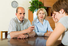 Adult daughter talking with parents. Adult daughter having serious talking with mature parents at the table at home royalty free stock image