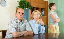 Adult daughter talking with parents. Adult daughter and mature parents having serious talking at home stock images