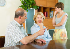 Adult daughter talking with parents. Adult daughter and mature parents having serious talking in home interior stock image