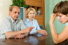 Adult daughter talking with parents. Mature parents and adult daughter having serious talking in home interior stock photography