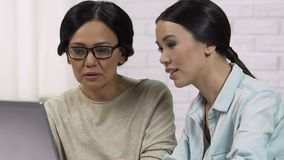 Adult daughter teaching mom to use computer, helping to register on website. Stock footage stock footage