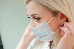 Adult dentist puts a protective mask on her mouth. royalty free stock image