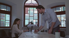 Adult designer and assistant sitting at the desk. Two architect working in the creative office. Woman typing on laptop, man reading building plan writing notes stock video footage