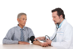Adult doctor checking pressure of old patient. Stock Image