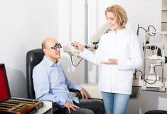 Adult doctor examinating eyesight Royalty Free Stock Photos